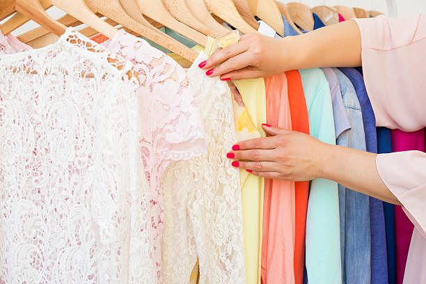 woman looking at the clothing rack - garment stock photos and pictures
