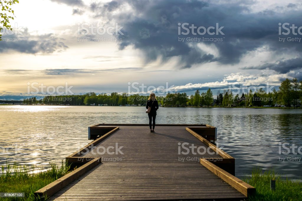 Woman looking at the lake stock photo