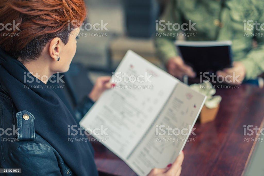 Woman looking at the menu stock photo