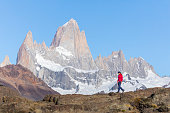 A woman is standing  on a clifftop above El Chalten looking over to Mount Fitz Roy in Los Glaciares National park