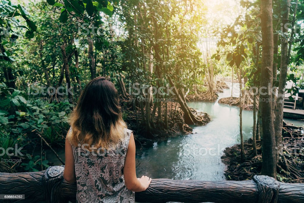 Woman looking at the river in tropical forest stock photo