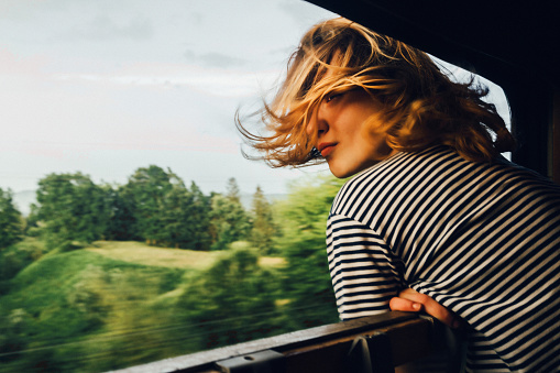 Caucasian woman looking at the view from train window