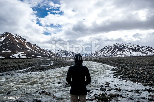 Woman looking at Toklat river with mountain range in background in Denali National Park, Alaska