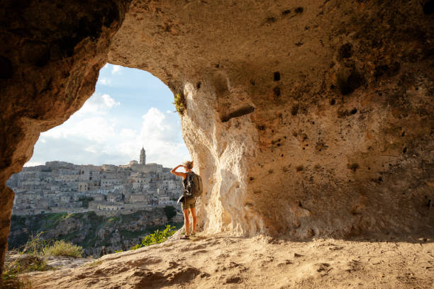 Woman looking at view from a cave of Matera, Basilicata, Italy Matera, European Capitals of Culture 2019 matera italy stock pictures, royalty-free photos & images