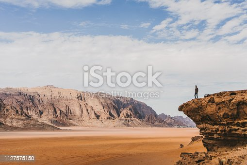 Young Caucasian woman  looking at  Wadi Rum desert  from above at sunset