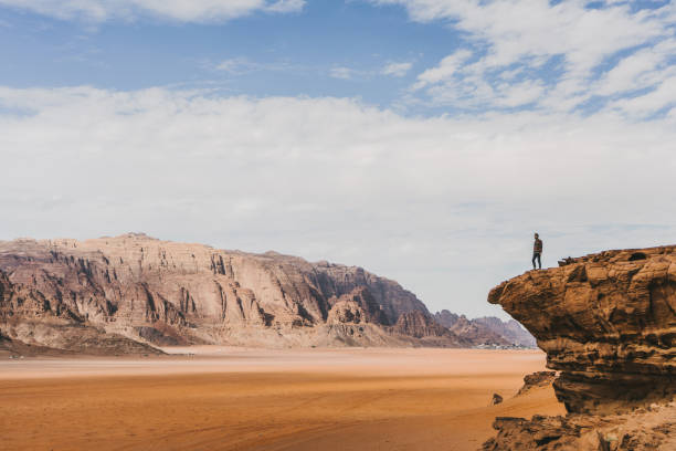 Woman looking at  Wadi Rum desert from rock stock photo