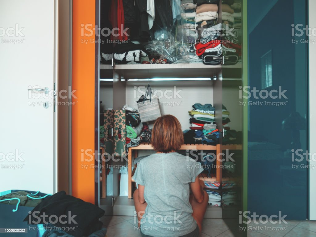 Woman looking at wardrobe, home interior, desperate housewife, cleaning home, rear view sitting, toned vintage style. royalty-free stock photo