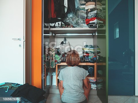 Woman looking at wardrobe, home interior, desperate housewife, cleaning home, rear view sitting, toned vintage style.