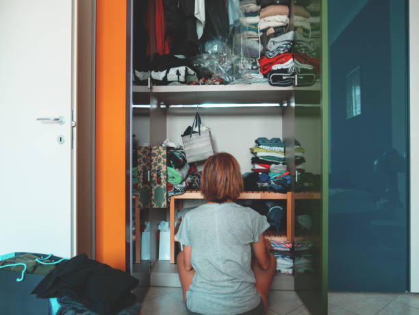 Woman looking at wardrobe, home interior, desperate housewife, cleaning home, rear view sitting, toned vintage style. stock photo