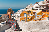 istock Woman looking away at the view of Oia town and the sea 1280501020