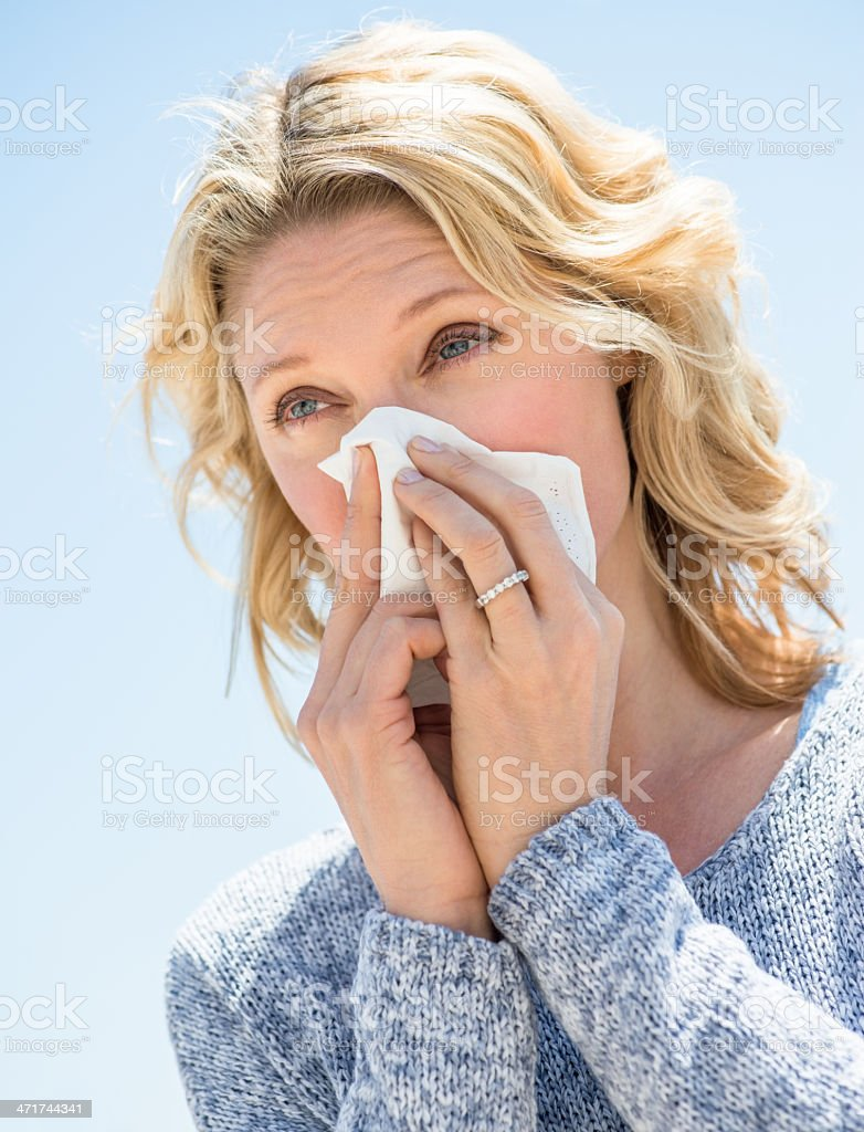 Woman Looking Away While Blowing Nose Against Clear Sky stock photo