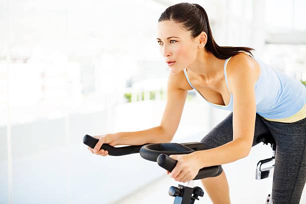 frau wegsehen beim training auf dem fahrrad im fitness-center - herumwirbeln frau stock-fotos und bilder
