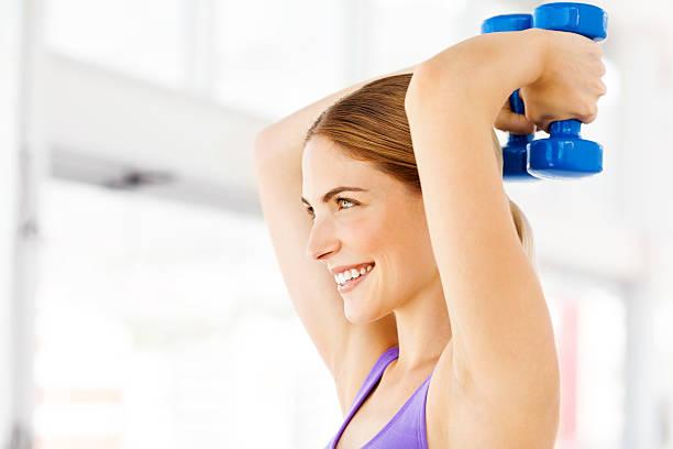 Frau Wegsehen beim Training mit Hanteln im Fitnessstudio – Foto
