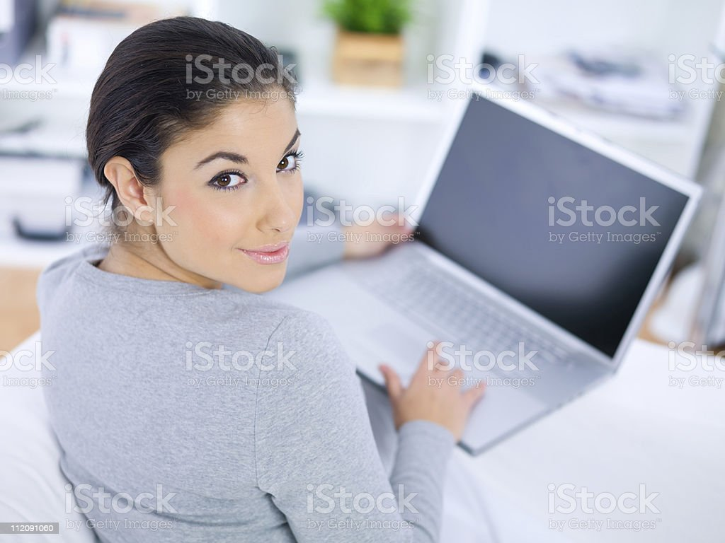 Woman looking back over her shoulder at camera using laptop royalty-free stock photo