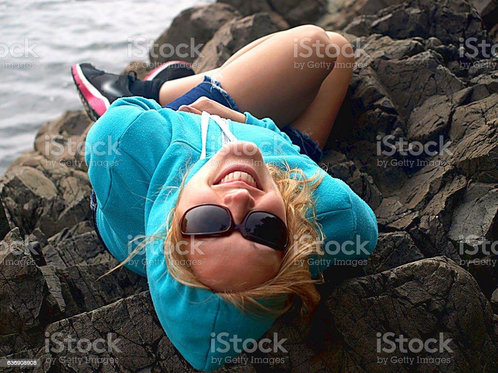 Woman looking back over shoulders on rocky Tofino Coastline stock photo