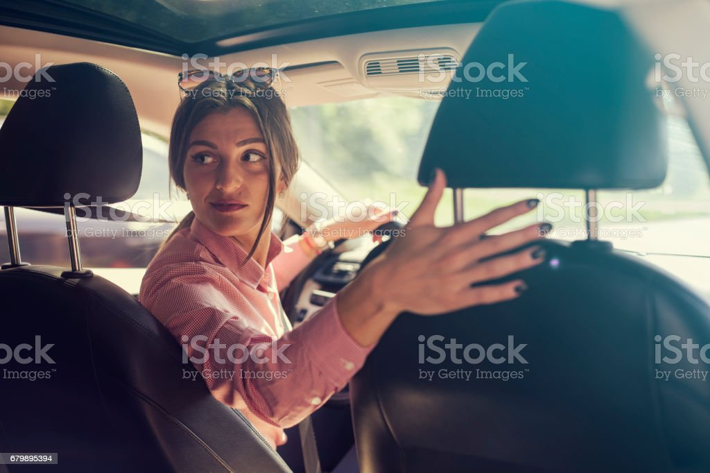 Woman looking back while reversing stock photo