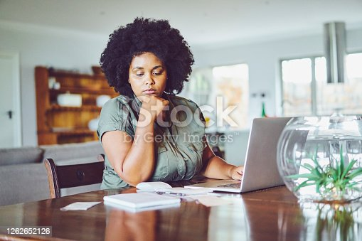 Woman looking concerned while going over bills while online banking with a laptop in her living room ath ome