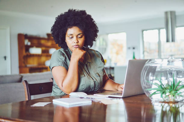 Woman looking concerned while paying bills from home stock photo