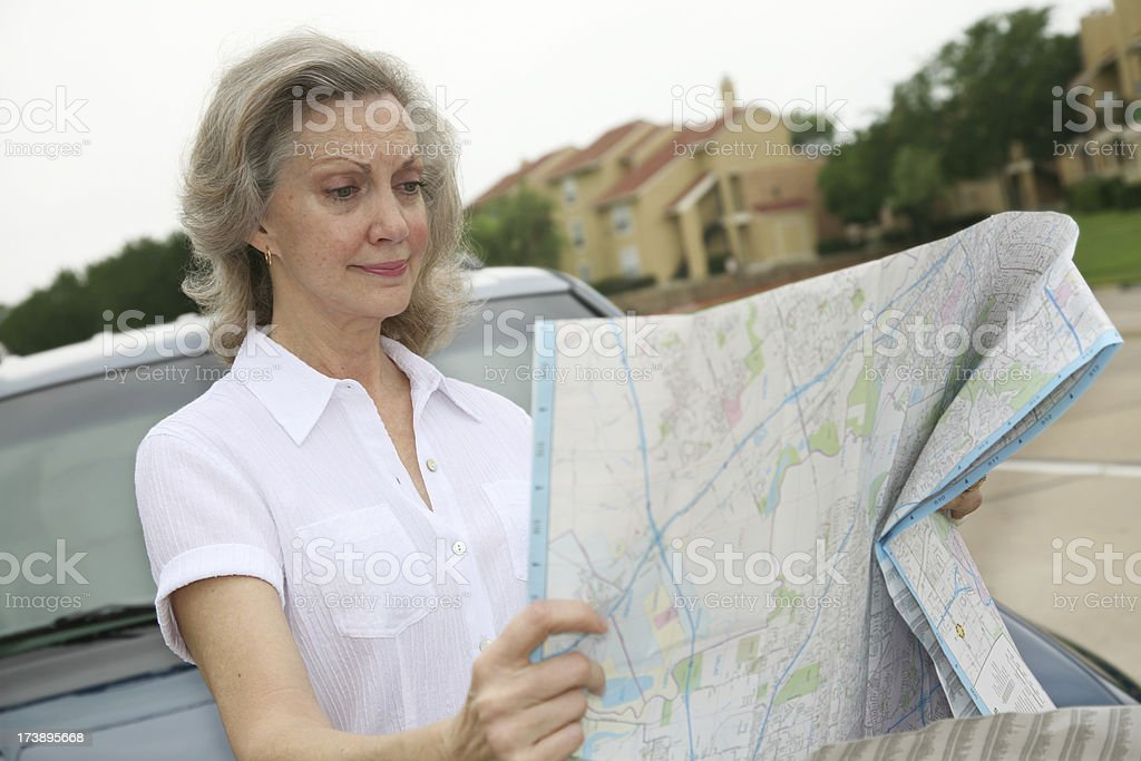 Woman Looking Confused with Map Out in Front of Car royalty-free stock photo