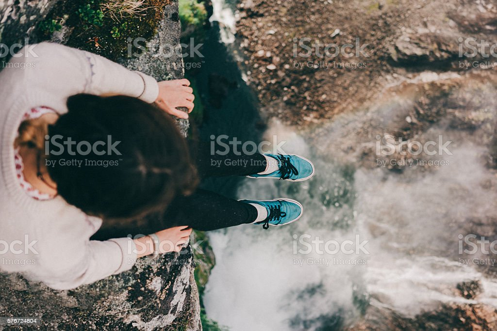 Woman looking down at the waterfall stock photo