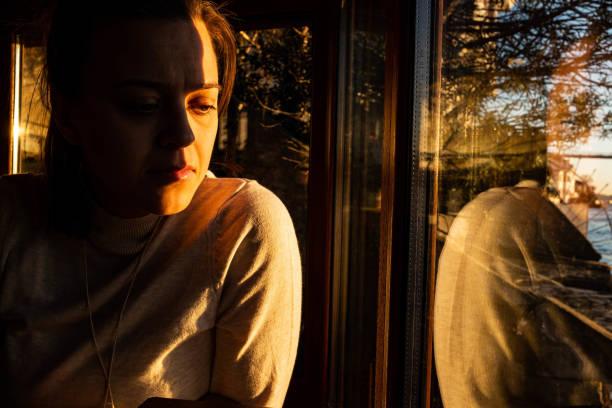 Frau schaut durch das Fenster nach unten – Foto
