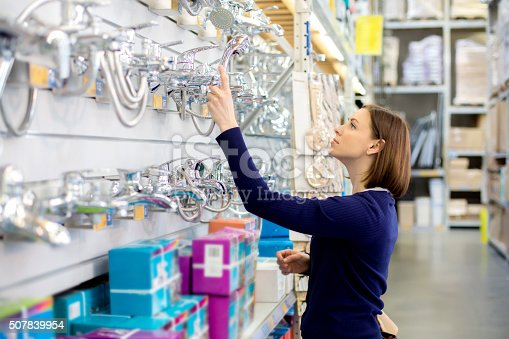 woman looking faucets at plumbing store