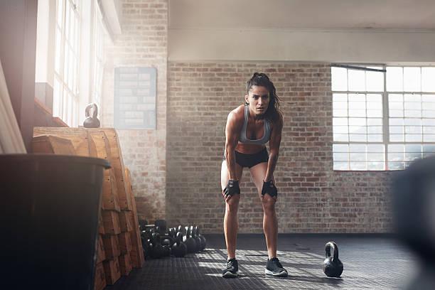 frau schaut sich um ihre fitness training - konzentrationsübungen stock-fotos und bilder