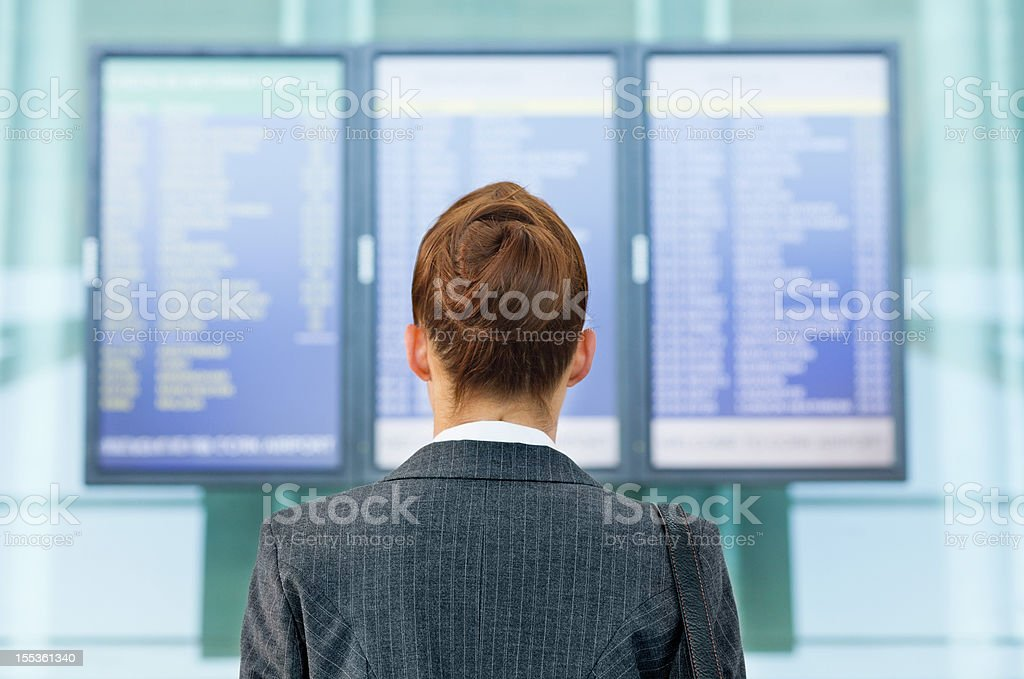 Woman Looking for Flight Information at Airport royalty-free stock photo