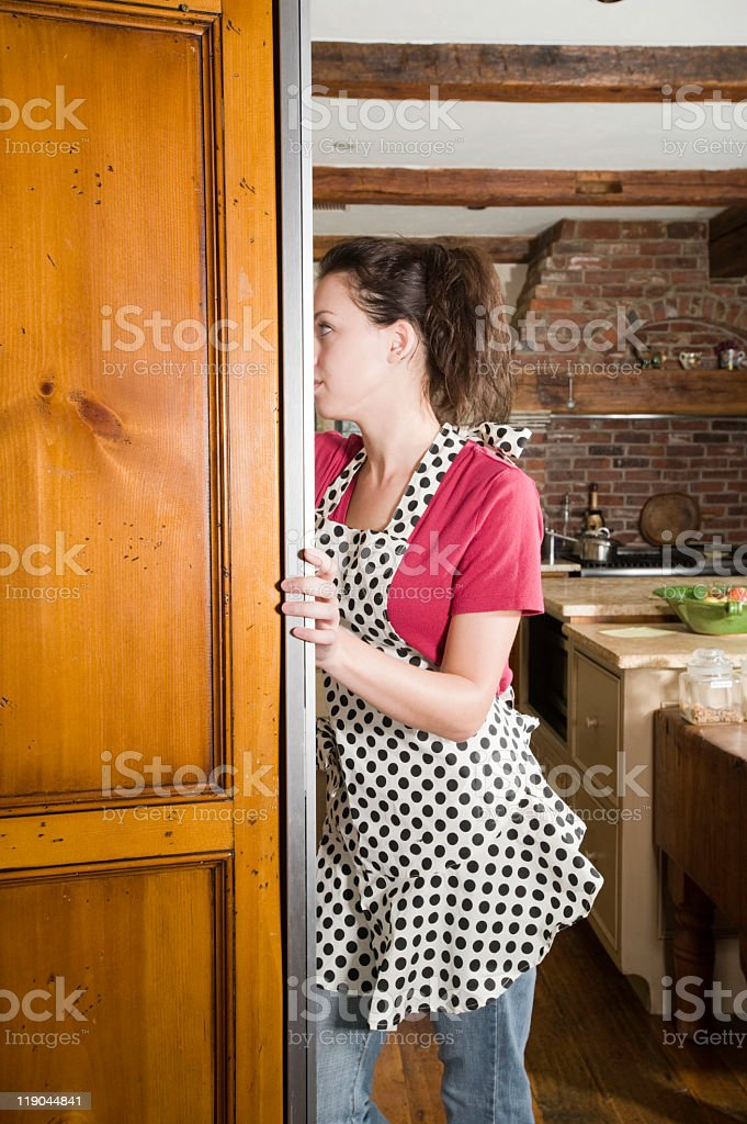 Woman looking for food in the refrigerator stock photo