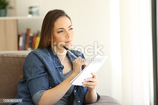 694187664istockphoto Woman looking for inspiration writing in a notebook 1030850320