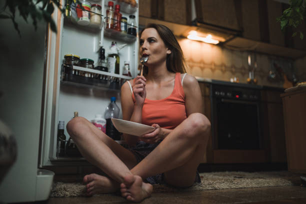 Woman looking for midnight snack in the refrigerator stock photo