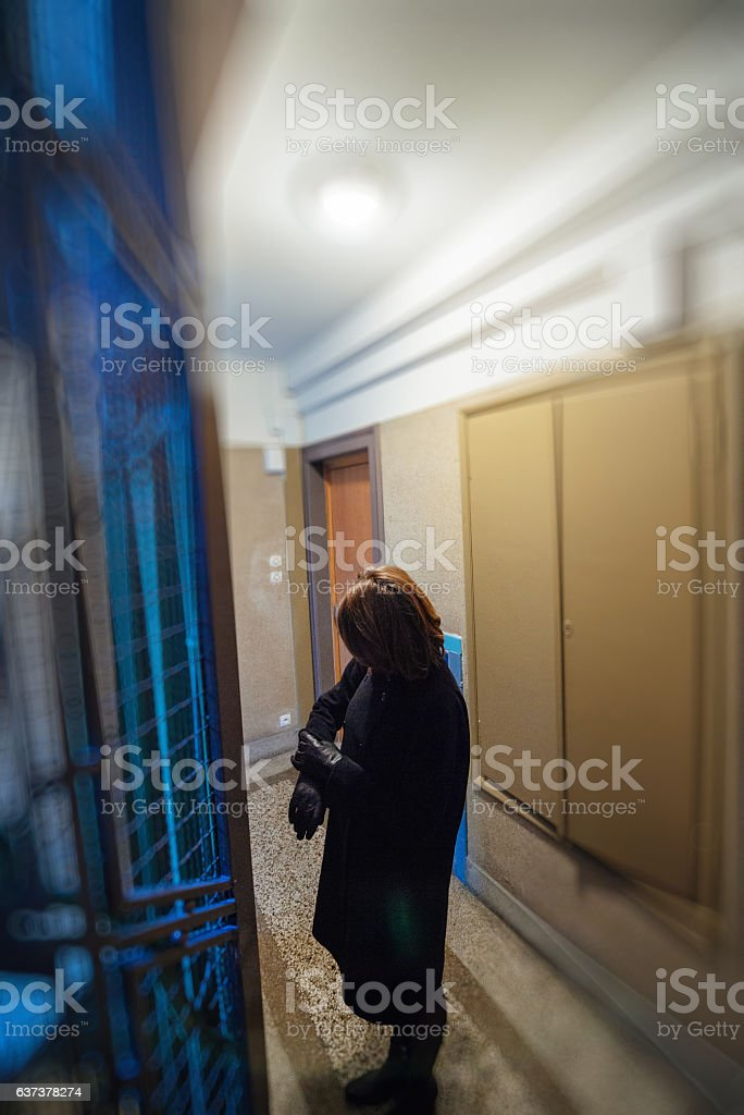 Woman looking for time waiting for elevator stock photo