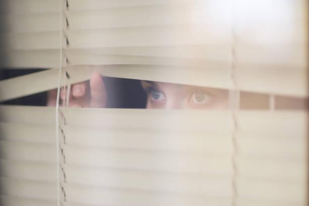 mujer mirando hacia adelante a través de las persianas de la ventana - foto de stock