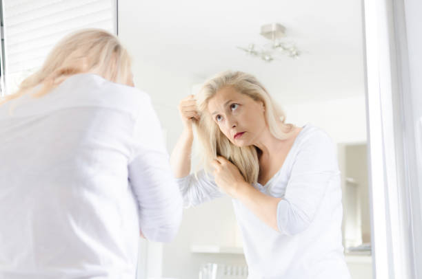 Woman looking hair in a mirror stock photo