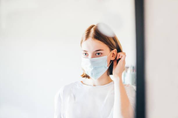 vrouw die zich in de spiegel kijkt - mirror mask stockfoto's en -beelden