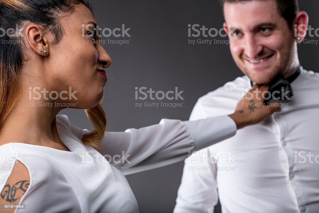 woman looking his man and taking him by the tie stock photo