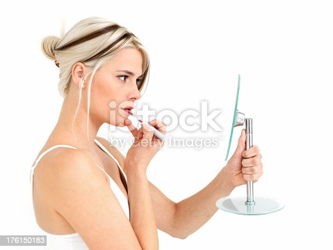 109721176istockphoto Woman looking in a mirror, applying lipgloss 176150183