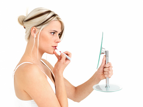 109721176 istock photo Woman looking in a mirror, applying lipgloss 176150183