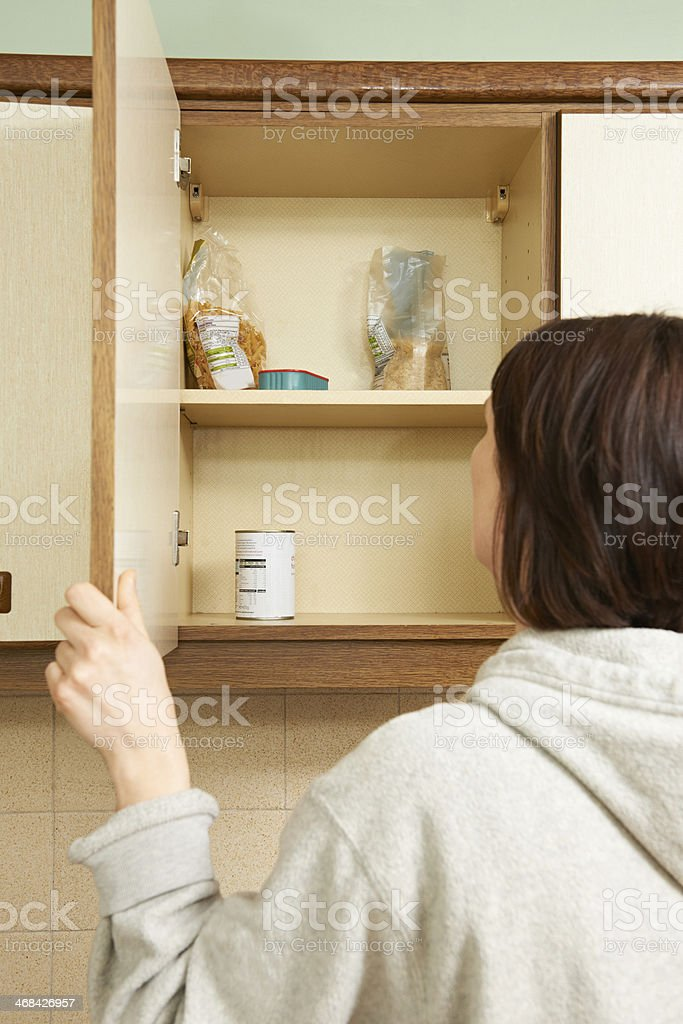 Woman Looking In Empty Food Cupboards stock photo