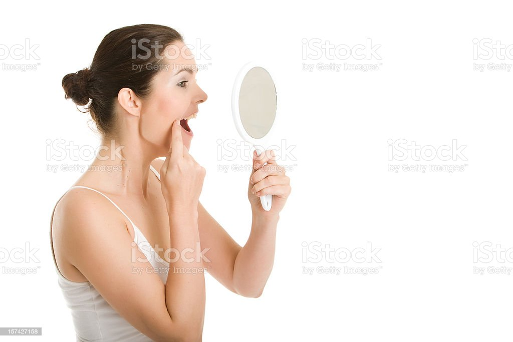 Woman looking in hand mirror stock photo