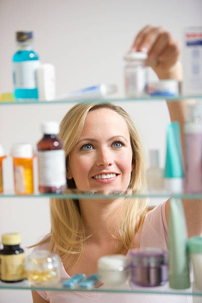 Woman Looking in Medicine Cabinet stock photo