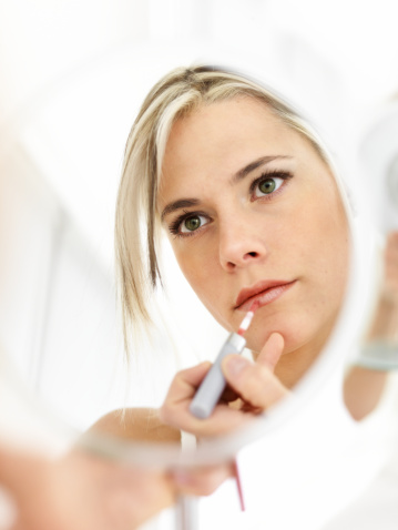 109721176 istock photo Woman looking in mirror, applying lipgloss 109721166