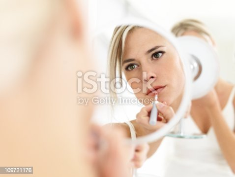 istock Woman looking in mirror, applying lipgloss 109721176