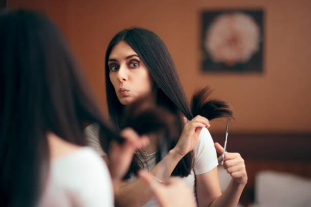 frau blick in spiegel schneiden split haarendeten - cut wrong hair stock-fotos und bilder