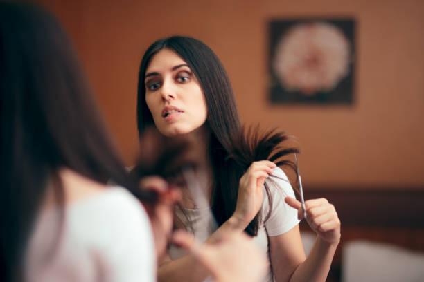 kobieta patrząc w lustro cięcie split włosy kończy - ciąć zdjęcia i obrazy z banku zdjęć