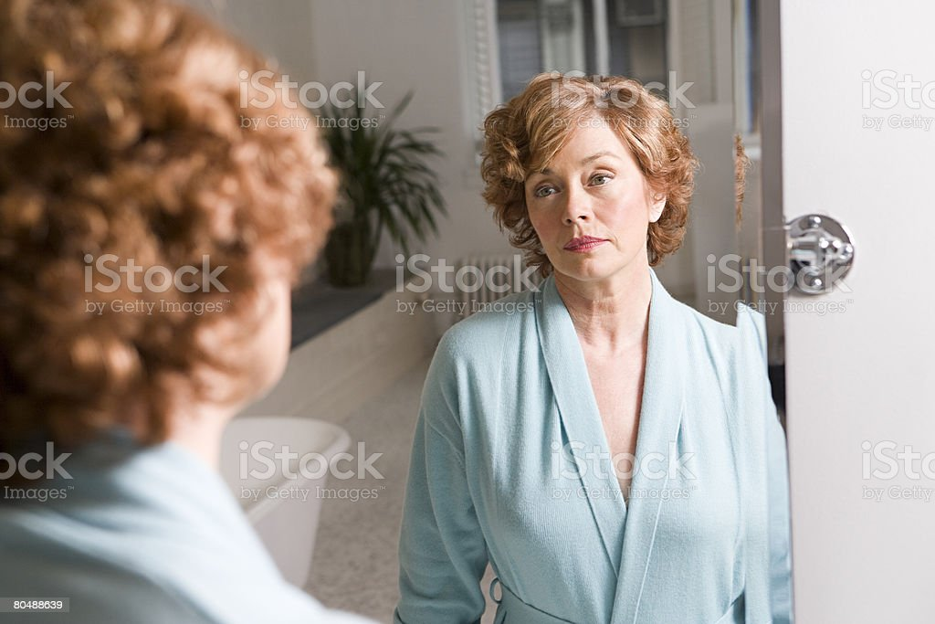 Woman looking in mirror 免版稅 stock photo