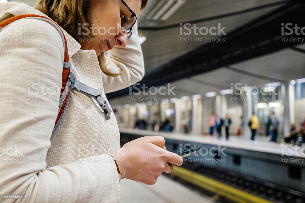 Woman looking in smartphone waiting for Metro stock photo