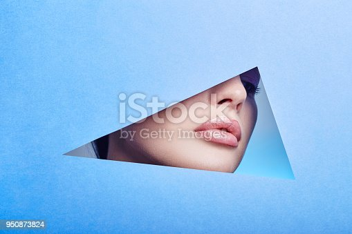 istock Woman looking in the hole, bright beautiful makeup, big eyes and lips, bright lipstick, professional cosmetics and facial care. Bright colored background and a gap slot in the paper 950873824