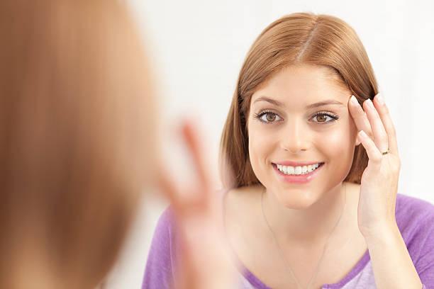 frau schaut in den spiegel nach einer schönheitsbehandlung. - lustige augenbrauen stock-fotos und bilder