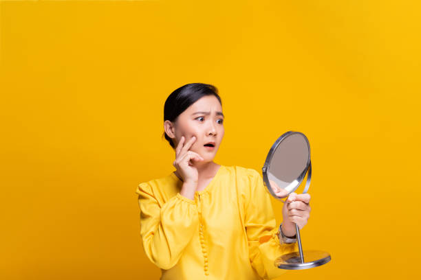 Woman looking in the mirror and worried the wrinkles on her face stock photo